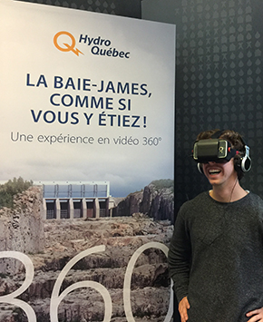Teacher experiencing the immersive 360° video of the Robert-Bourassa generating facility with a virtual reality headset at the Hydro-Québec booth.